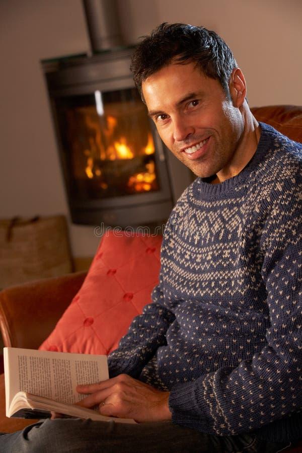 Mann, der mit Buch durch Cosy Protokoll-Feuer sich entspannt lizenzfreie stockfotos