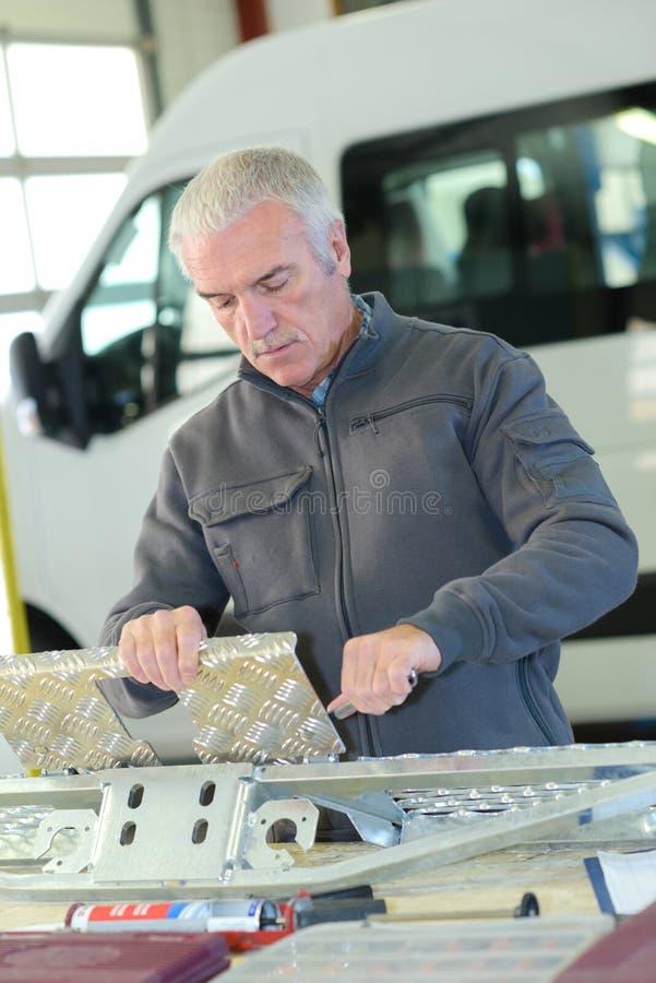 Mann, der mit checkerplate arbeitet lizenzfreies stockbild