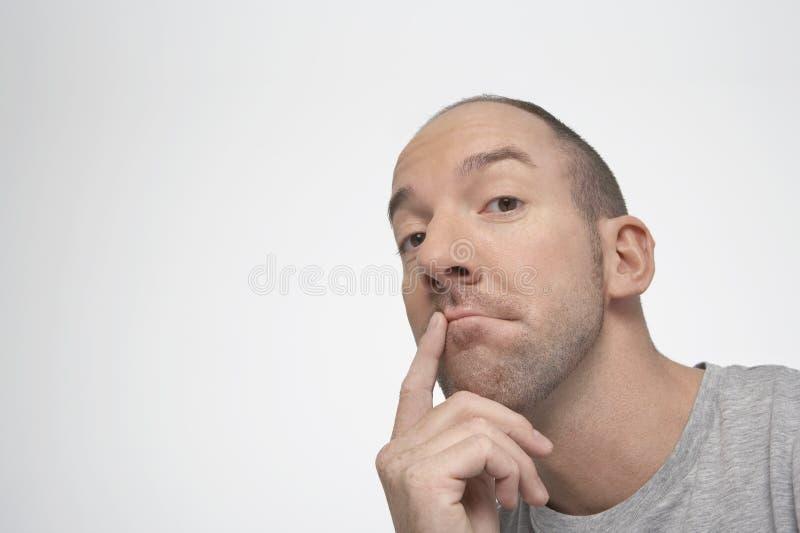 Mann, der mit dem Finger auf Lippen denkt lizenzfreies stockfoto