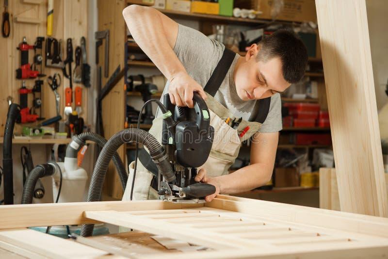 Mann, der mit dem Schnitzen der Ausrüstung an der Werkstatt arbeitet Chinselings-Nut lizenzfreies stockbild