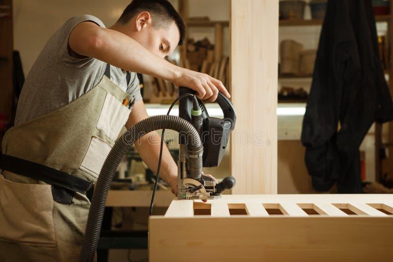 Mann, der mit dem Schnitzen der Ausrüstung an der Werkstatt arbeitet Chinselings-Nut stockfotos
