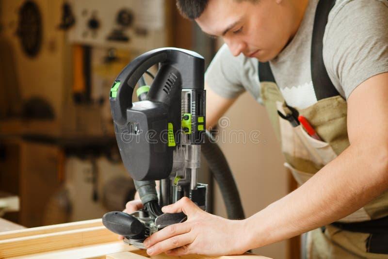 Mann, der mit dem Schnitzen der Ausrüstung an der Werkstatt arbeitet Chinselings-Nut stockbilder