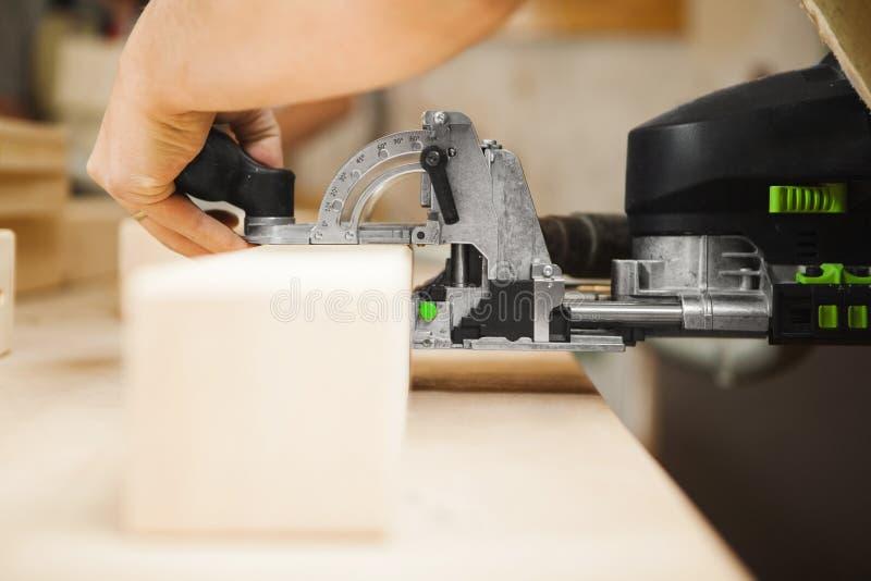 Mann, der mit dem Schnitzen der Ausrüstung in der Werkstatt arbeitet Elektronisches Gerät lizenzfreies stockbild