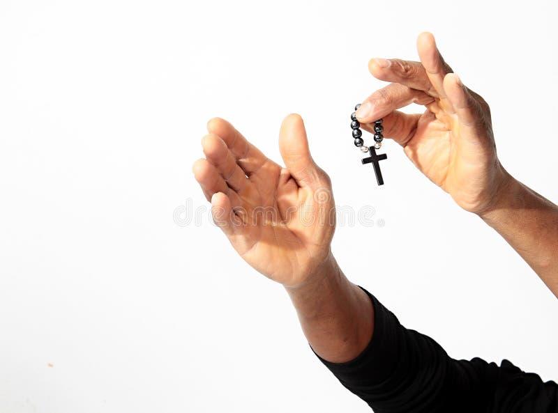 Mann, der mit den Armen ausgestreckt betet und ein Kreuz hält stockfoto