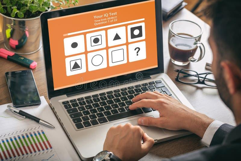 Mann, der mit einem Computerlaptop, IQ-Testform auf Schirm, Bürohintergrund arbeitet lizenzfreie abbildung