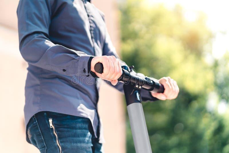 Mann, der mit einem elektrischen Roller in der Stadt fährt Geschäftsmann, der E-Kick-Fahrzeug auf der Straße fährt lizenzfreies stockfoto