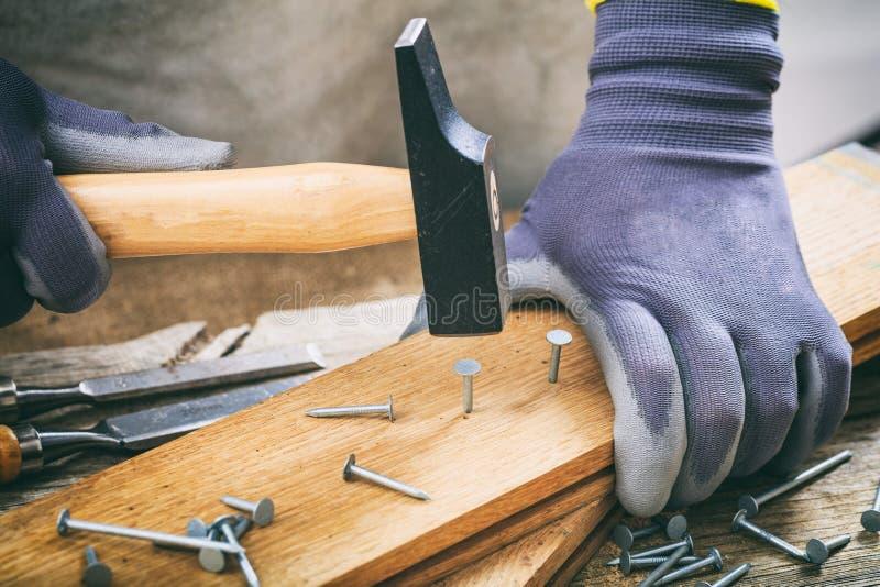 Mann, der mit einem Hammer arbeitet stockfotografie