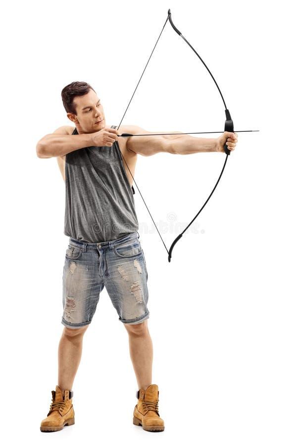 Mann, der mit einem Pfeil und Bogen zielt stockfoto