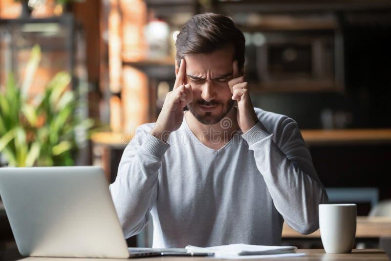 Mann, der mit der Fingerstirn denkt oder leidet unter Kopfschmerzen sich berührt lizenzfreies stockbild