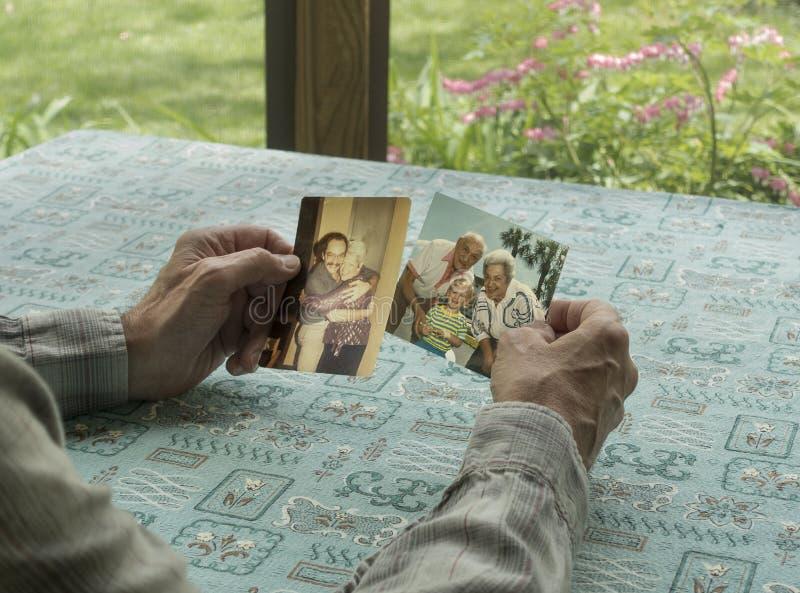 Mann, der mit Fotos sich in Erinnerungen ergeht stockfoto