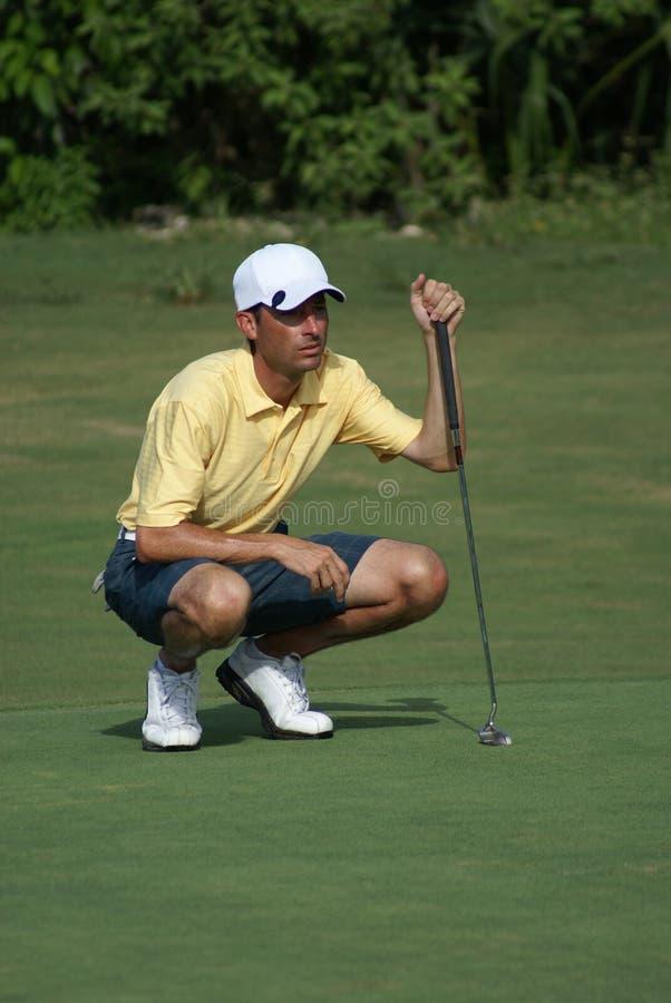 Mann, der mit gelbem Hemd Golf spielt stockbilder