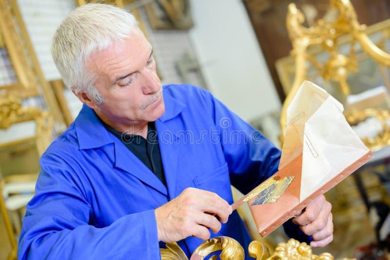 Mann, der mit Goldblatt arbeitet stockfotografie