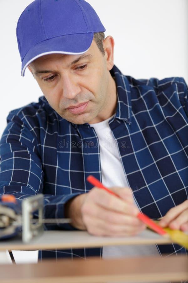 Mann, der mit hölzernem messendem Band arbeitet und mit Bleistift markiert lizenzfreie stockfotografie