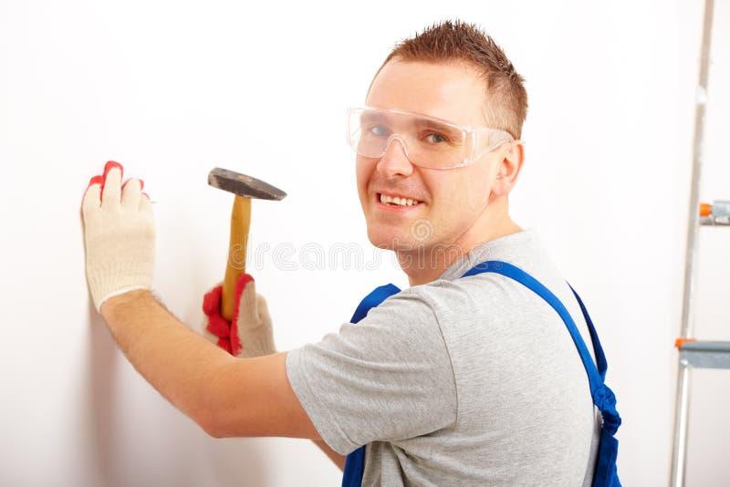 Mann, der mit Hammer arbeitet lizenzfreie stockbilder