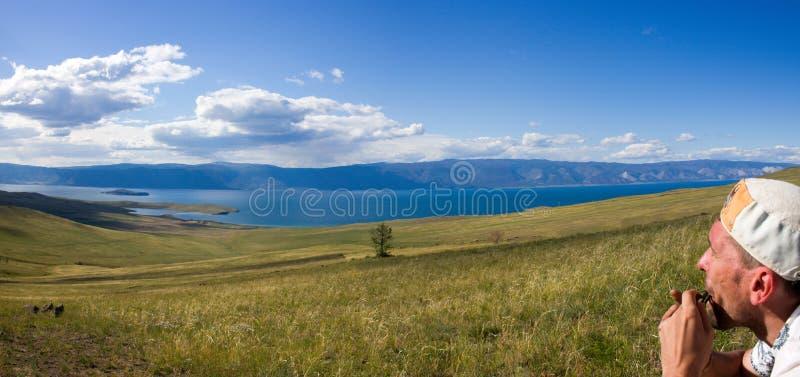 Mann, der mit khomus in Olkhon-Insel auf Baikal See spielt lizenzfreies stockfoto