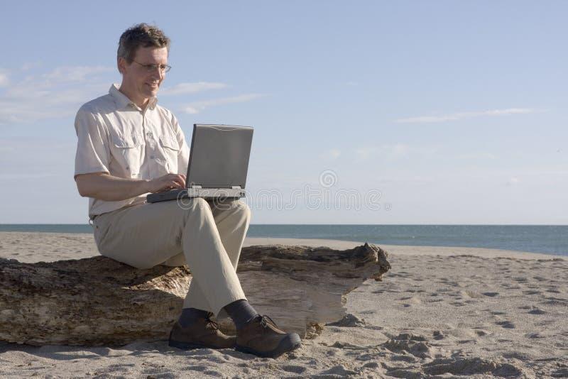 Mann, der mit Laptop auf Strand arbeitet lizenzfreie stockfotos