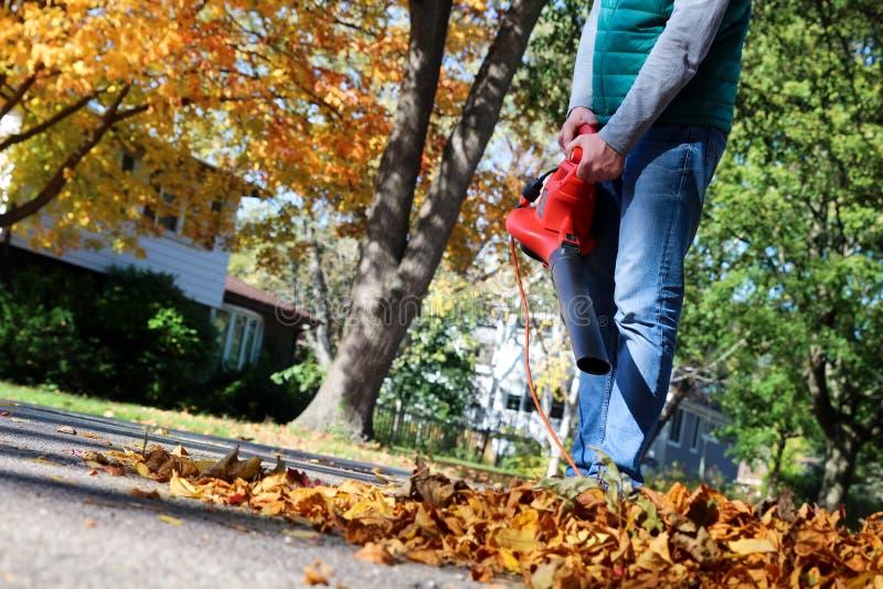 Mann, der mit Laubsauger arbeitet: die Blätter werden auf und ab an einem sonnigen Tag gewirbelt lizenzfreie stockfotos