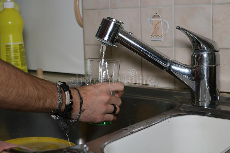 Mann, der mit Leitungswasserglas füllt stockbild