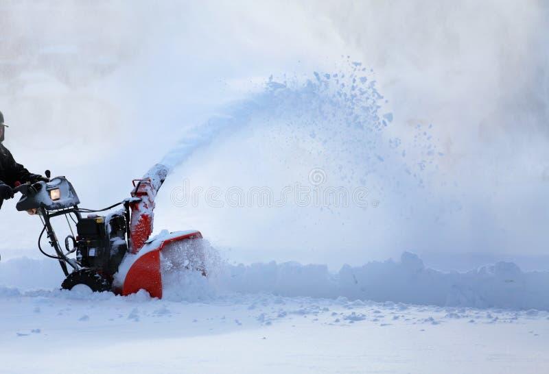 Mann, der mit Schneefräse arbeitet lizenzfreie stockfotografie