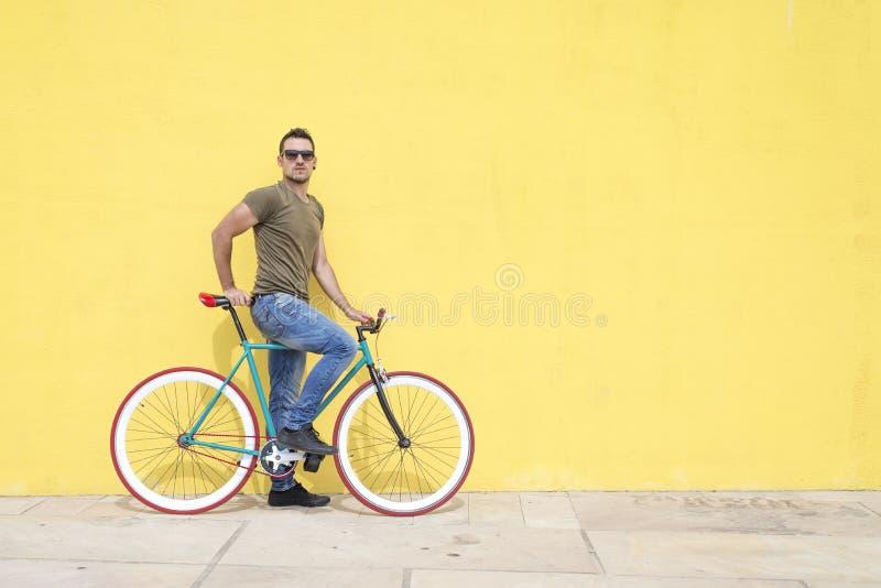Mann, der mit seinem örtlich festgelegten Gangfahrrad aufwirft lizenzfreies stockfoto