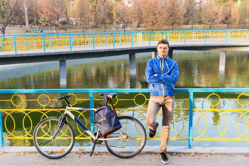 Mann, der mit seinem Fahrrad wartend steht stockbilder