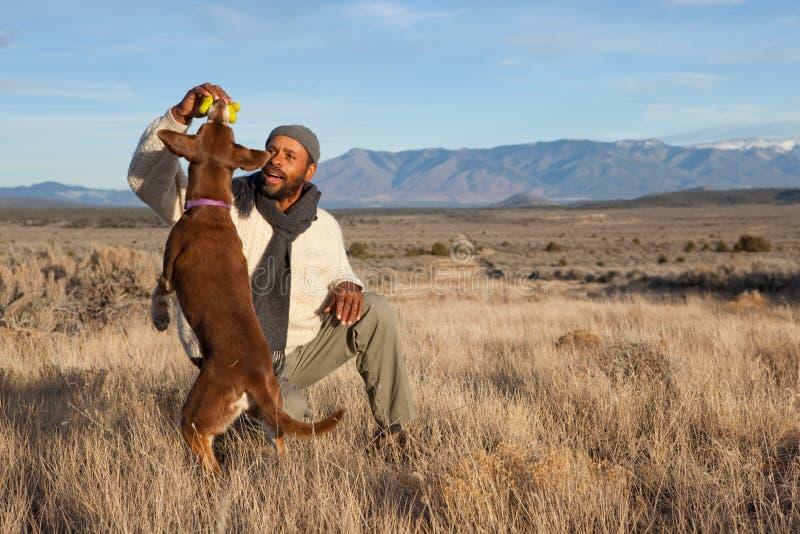 Mann, der mit seinem Hund spielt lizenzfreie stockfotos
