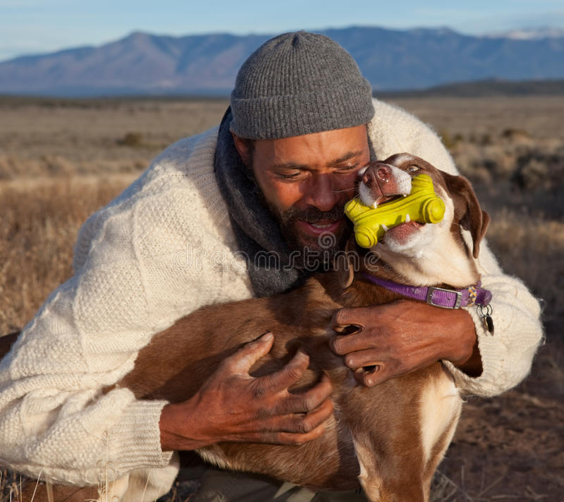 Mann, der mit seinem Hund umarmt und spielt lizenzfreie stockfotos