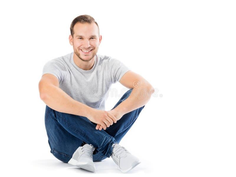 Mann, der mit seinen Beinen gekreuzt sitzt Lächelnder Kerl stockfotos