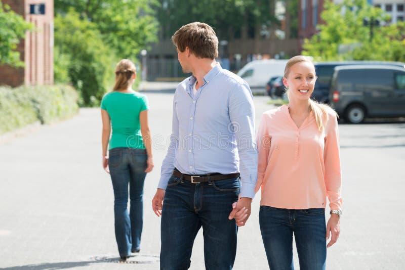 Mann, der mit seiner Freundin betrachtet eine andere Frau geht stockfotos