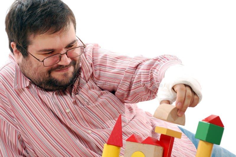 Mann, der mit Spielzeugziegelsteinen spielt stockbild