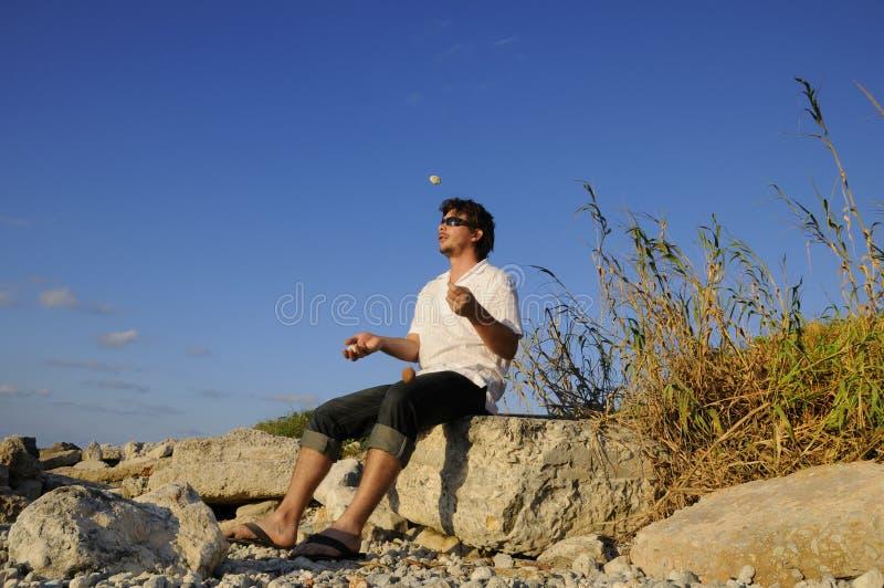 Mann, der mit Steinen jongliert lizenzfreie stockfotografie