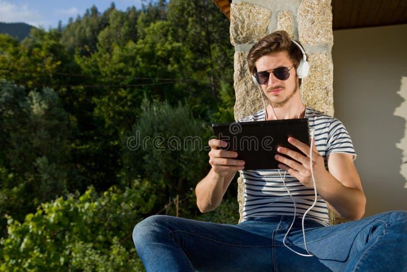 Mann, der mit Tabletten-PC sich entspannt lizenzfreie stockfotografie
