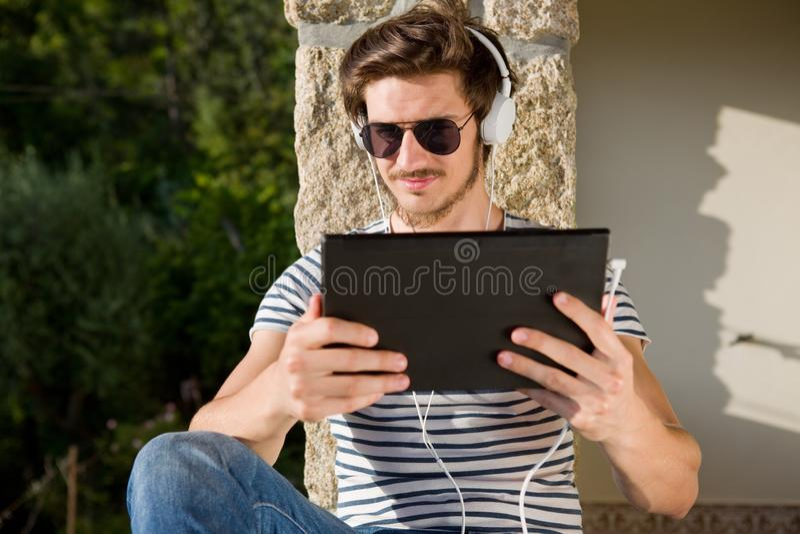 Mann, der mit Tabletten-PC sich entspannt lizenzfreies stockfoto