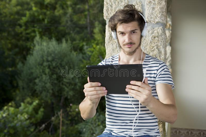 Mann, der mit Tabletten-PC sich entspannt stockfotos