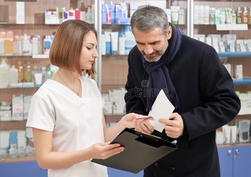 Mann, der mit weiblichem Chemiker im Drugstore sich berät stockfoto