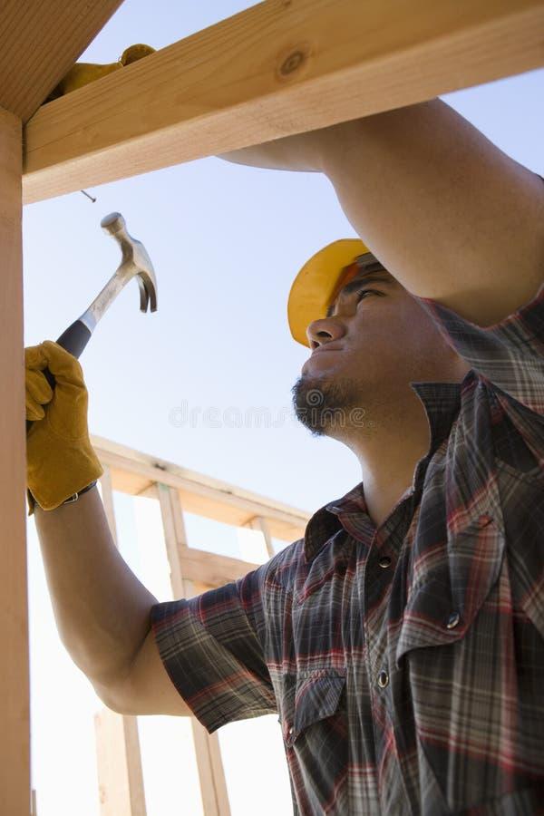 Mann, der Nagel am Standort hämmert stockfotos