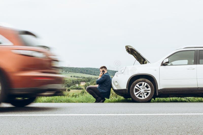 Mann, der nahe defektem Auto mit dem Telefon, nach Hilfe suchend sitzt stockbilder