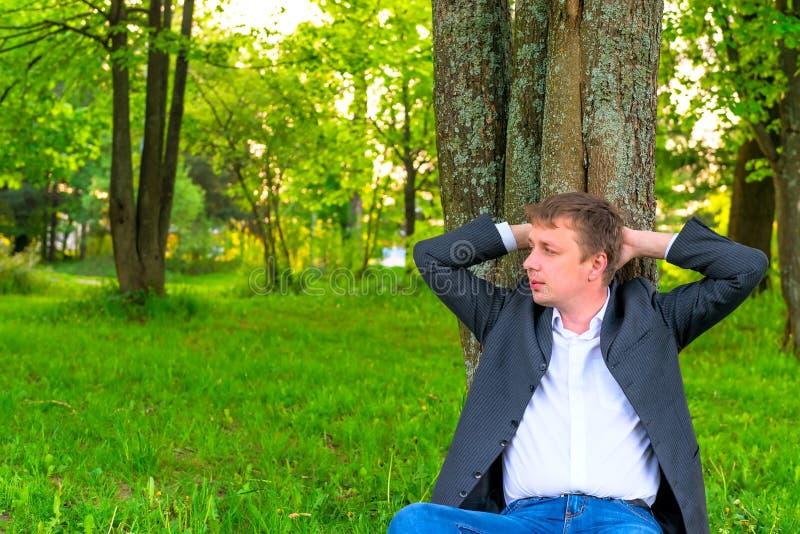 Mann, der nahe einem hohen Baum stillsteht stockbild
