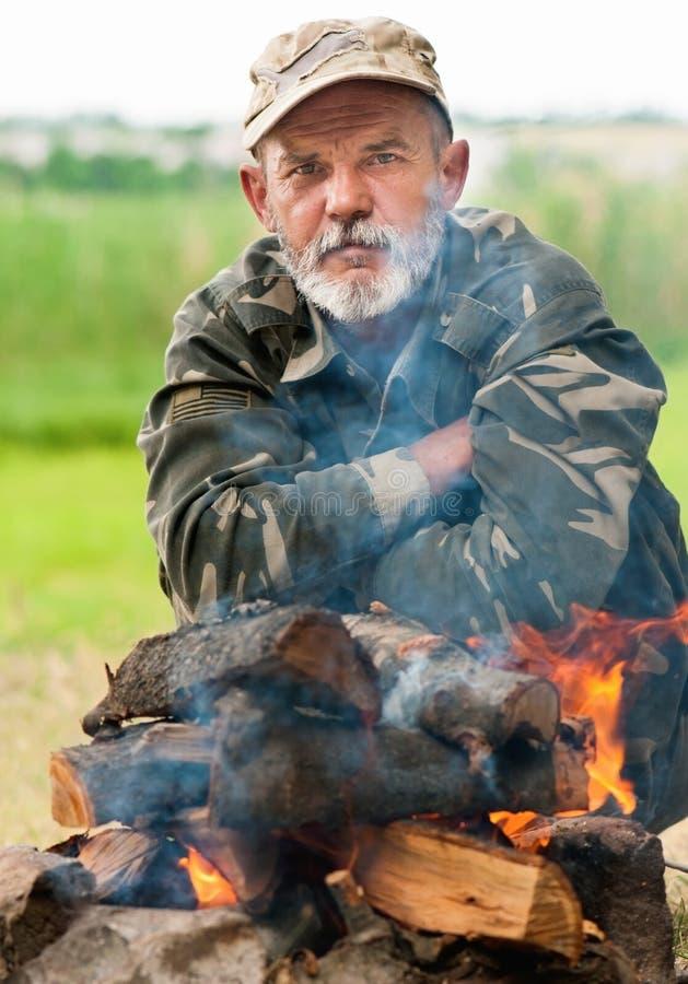 Mann, der nahe Feuer sitzt stockfoto