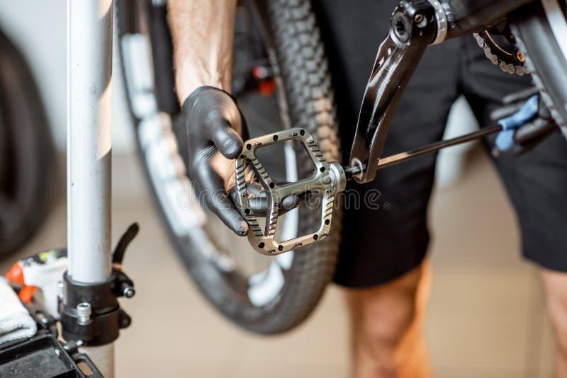 Mann, der neue Pedale auf ein Fahrrad installiert lizenzfreies stockbild