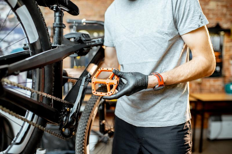 Mann, der neue Pedale auf ein Fahrrad installiert lizenzfreies stockfoto