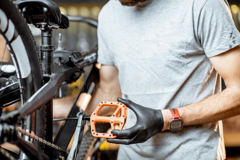 Mann, der neue Pedale auf ein Fahrrad installiert stockfotografie