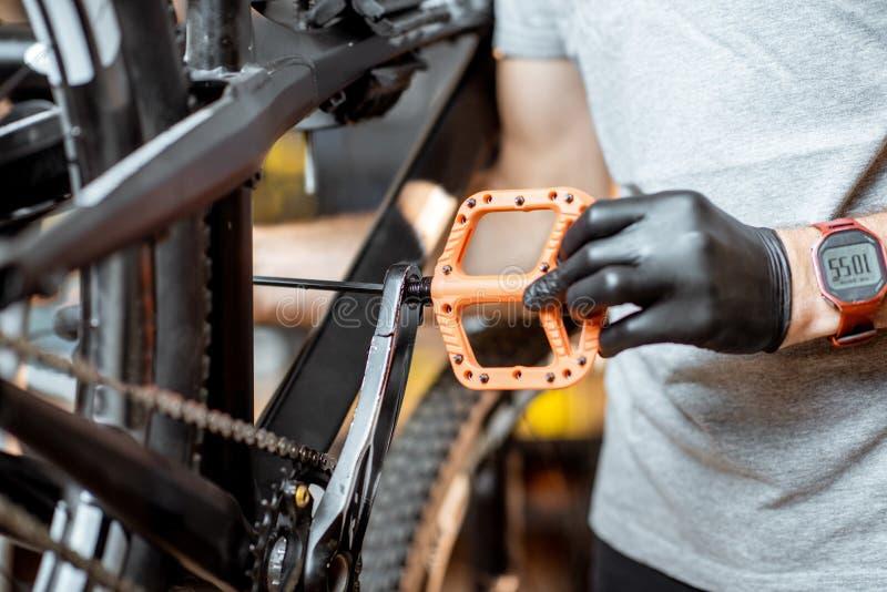 Mann, der neue Pedale auf ein Fahrrad installiert lizenzfreie stockfotografie