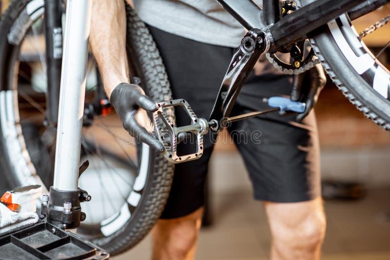 Mann, der neue Pedale auf ein Fahrrad installiert lizenzfreie stockfotos