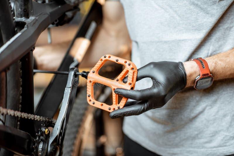 Mann, der neue Pedale auf ein Fahrrad installiert lizenzfreie stockbilder