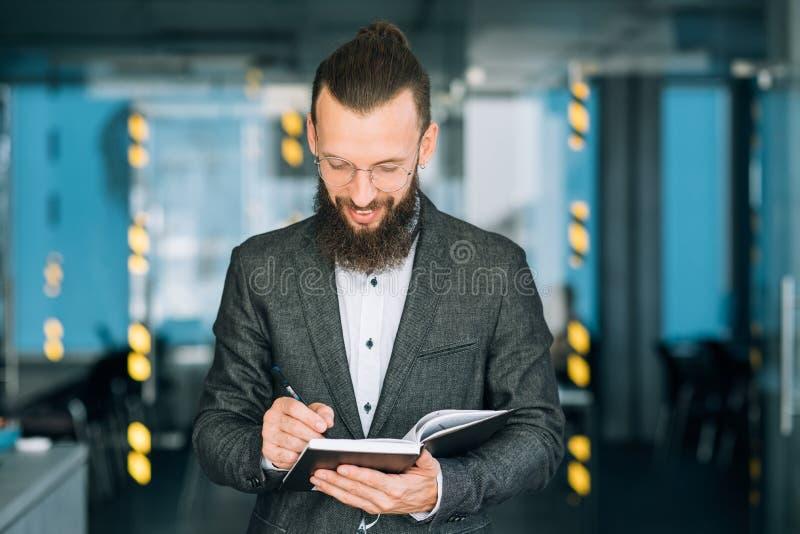 Mann, der Notizbuchgeschäfts-Tagesordnungszeitplan schreibt lizenzfreie stockfotos