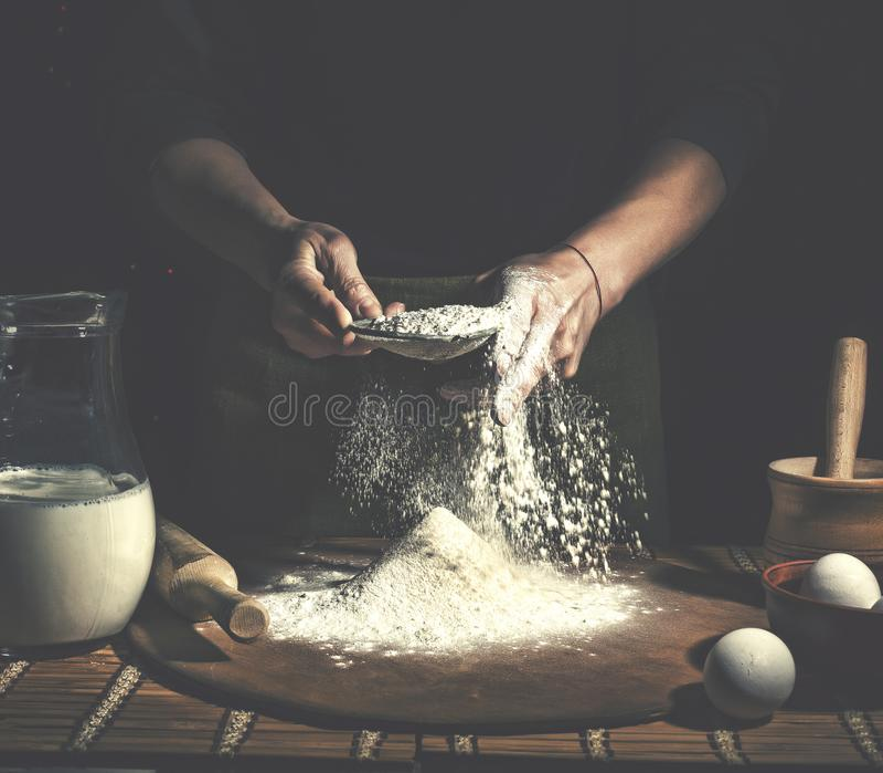 Mann, der oben Brotteig auf Holztisch in einem Bäckereiabschluß zubereitet Vorbereitung von Ostern-Brot lizenzfreie stockbilder