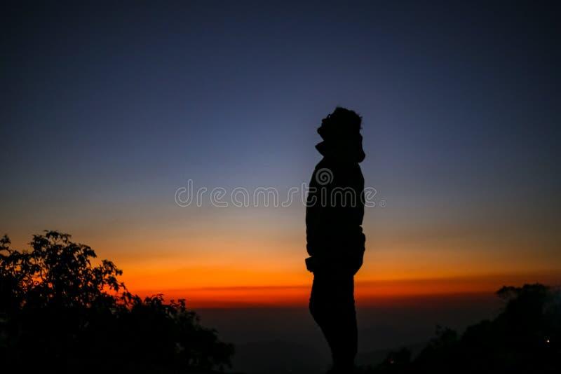 Mann, der oben Schattenbild steht und schaut stockbilder