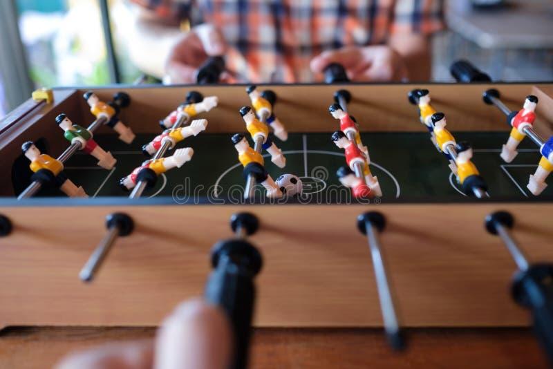 Mann, der oben Tischfußballfußballspielabschluß mit seinen Freunden spielt lizenzfreies stockfoto