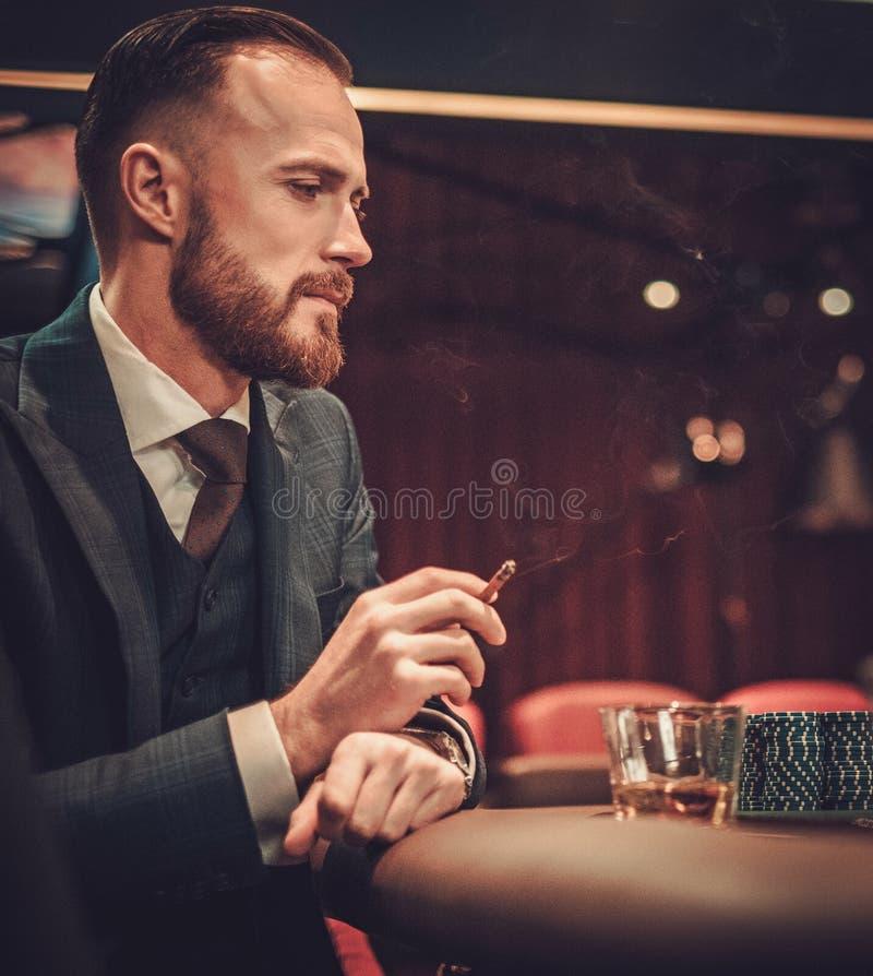 Mann der oberen Klasse, der in einem Kasino spielt lizenzfreie stockbilder